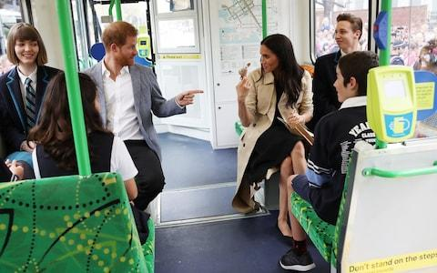 The Duke and Duchess of Sussex talk to students from Albert Park Primary School while riding a tram in Melbourne - Credit: Chris Jackson/Getty
