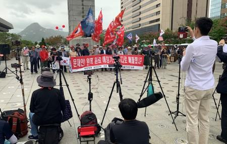 Mobile phones for a live broadcast film members of a conservative civic group taking part in a protest in Seoul