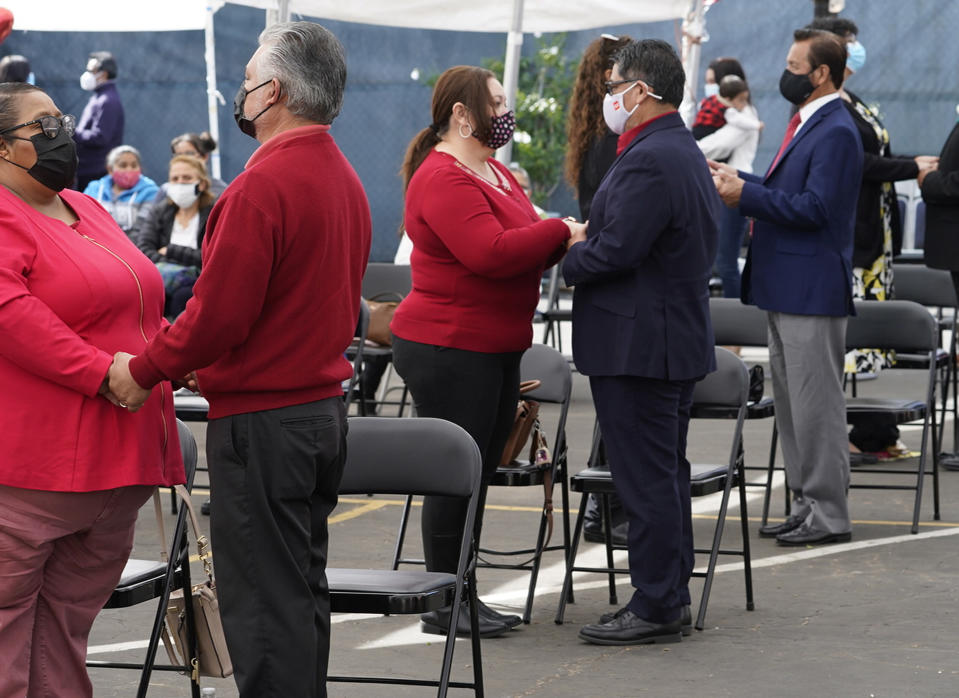Couples wear masks as they hold hands while renewing their marriage vows at Christ the King Roman Catholic Church in Los Angeles on Sunday, Feb. 14, 2021. (AP Photo/Damian Dovarganes)