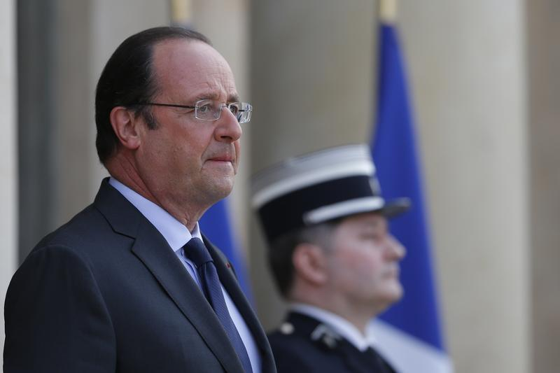 French President Francois Hollande attends to a guest at the steps of the Elysee Palace in Paris