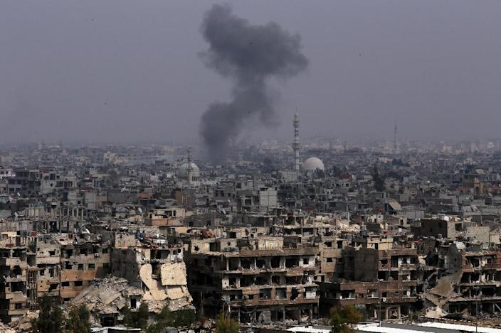 Smoke rises from buildings in Yarmuk, a Palestinian refugee camp on the edge of Damascus, during regime shelling targeting Islamic State group positions in the southern district of the capital on April 28, 2018 (AFP Photo/STRINGER)