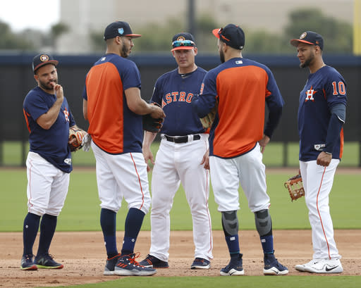 Houston Astros manager A.J. Hinch, center, speaks to Jose Altuve, left, Carlos Correa, second from left, Marwin Gonzalez, second from right, and Yuli Gurriel (10) during baseball spring training at The Ballpark of the Palm Beaches, Tuesday, Feb. 20, 2018, in West Palm Beach, Fla. (Karen Warren/Houston Chronicle via AP)
