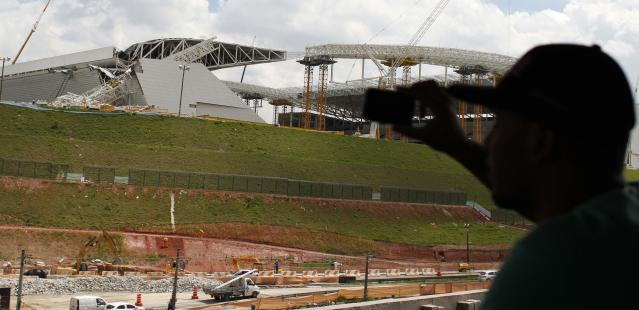 """A man takes a picture of a crane that collapsed on the site of the Arena Sao Paulo stadium, known as """"Itaquerao"""", which will host the opening soccer match of the 2014 World Cup, in Sao Paulo November 27, 2013. A crane collapsed on Wednesday at the construction site of a future World Cup soccer stadium in Sao Paulo, Brazil, killing at least three people and causing damage to the structure, local media said. REUTERS/Nacho Doce (BRAZIL - Tags: SPORT SOCCER DISASTER WORLD CUP)"""