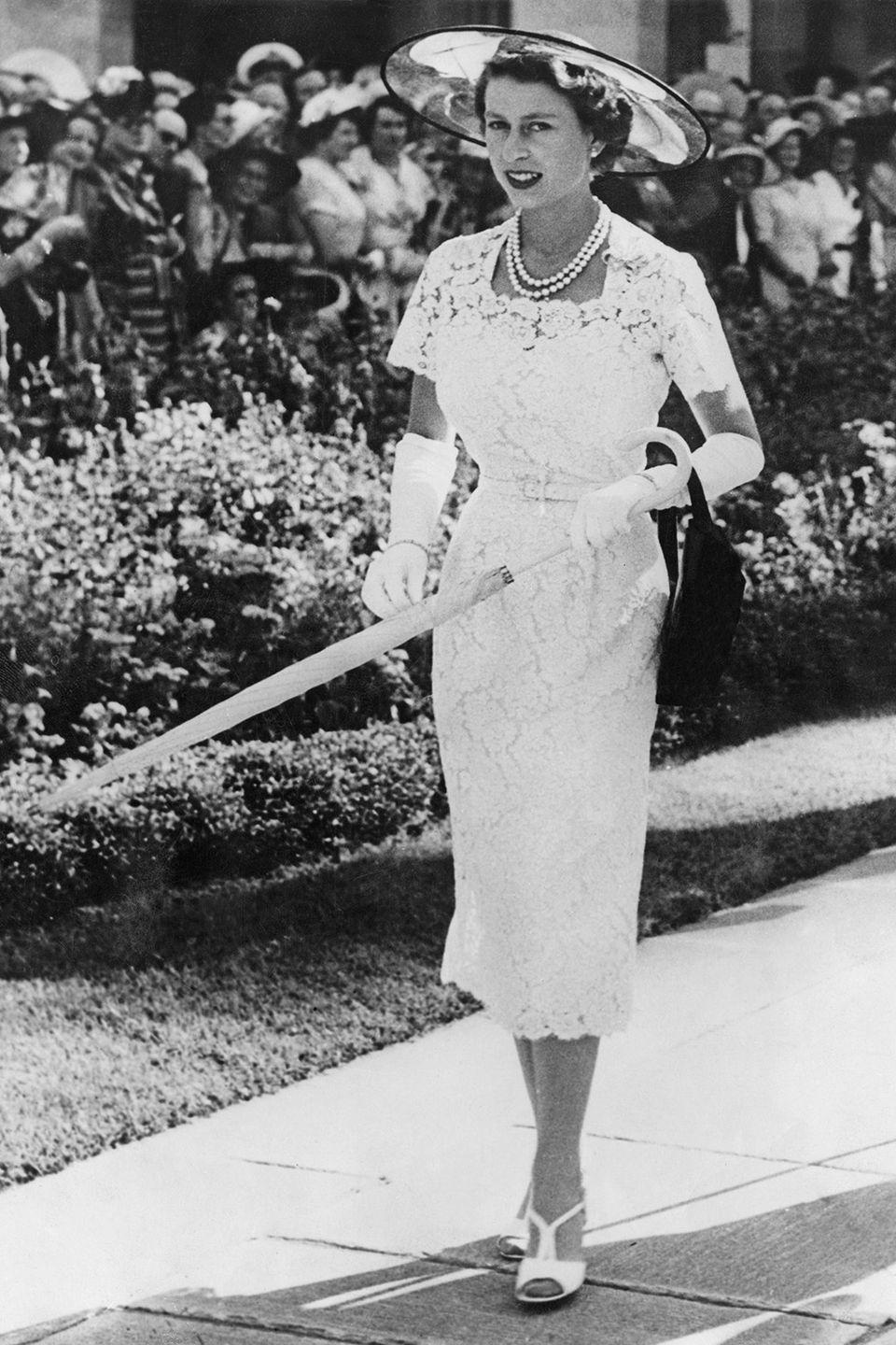 <p>In a garden wearing a fitted floral dress, white peep toe sandals, a pearl necklace, sun hat, and an umbrella. </p>