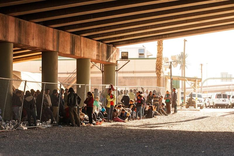 Migrants held in temporary fencing underneath the Paso Del Norte Bridge await processing on March 28, 2019 in El Paso, Texas. | Christ Chavez—Getty Images