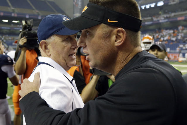 Oklahoma State coach Mike Gundy, right, talks with Texas San Antonio coach Larry Coker, left, following an NCAA college football game, Saturday, Sept. 7, 2013, in San Antonio. Oklahoma State won 56-35. (AP Photo/Eric Gay)