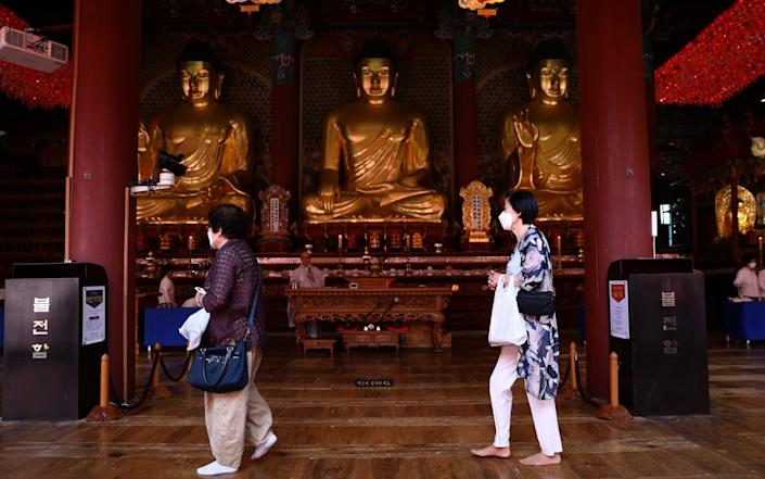 Worshippers wear face masks at the Jogyesa Temple in Seoul - Chung Sung-Jun/Getty Images Asia