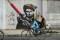 Cyclists peddle past a mural painted on the wall along a road in Kabul