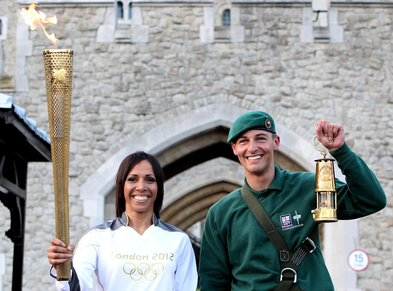 LONDON, ENGLAND - JULY 20:   Dame Kelly Holmes and Marine Martyn Williams (R) pose with the Olympic Torch and Olympic Flame as the flame arrives in London during the London 2012 Olympic Torch Relay on July 20, 2012 in London, England. The Olympic Flame is now on day 63 of a 70-day relay involving 8,000 torchbearers covering 8,000 miles. (Photo by Jan Kruger/Getty Images)
