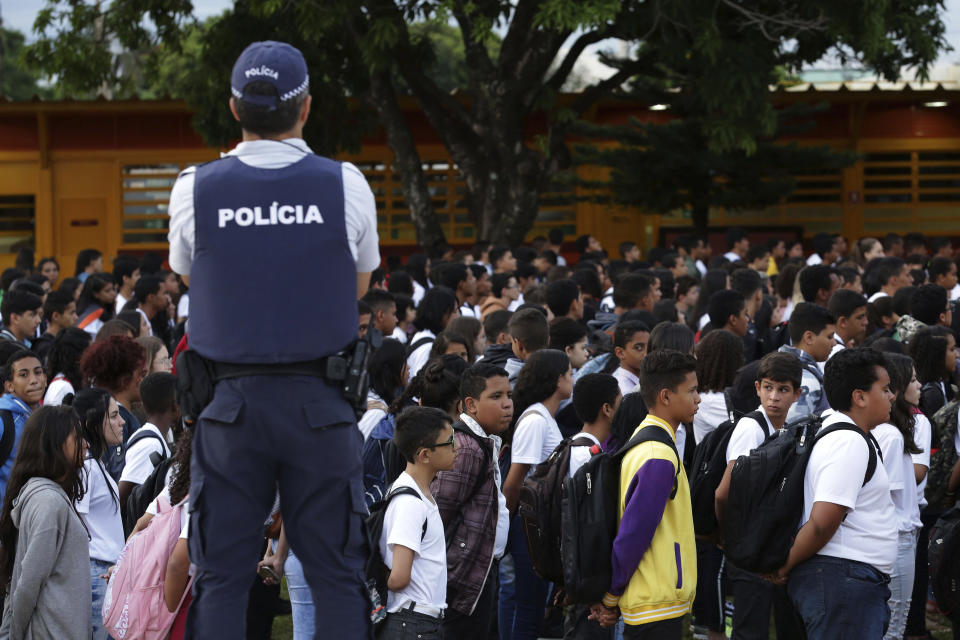 In this March 28, 2019 photo, a Military Police officer oversees students as they form up to sing the national anthem and raise the flag at the Ceilandia state school No. 7 in Brasilia, Brazil. Dressed in uniform, their arms tightly secured in their holsters, the officers summoned students to form ranks in the schoolyard. (AP Photo/Eraldo Peres)