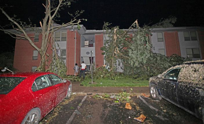 Residents walk toward Westbrooke Village Apartment building in Dayton, Ohio, on May 28. The tornado tore the roof off the building. (Photo: Doral Chenoweth III/Columbus Dispatch via AP)