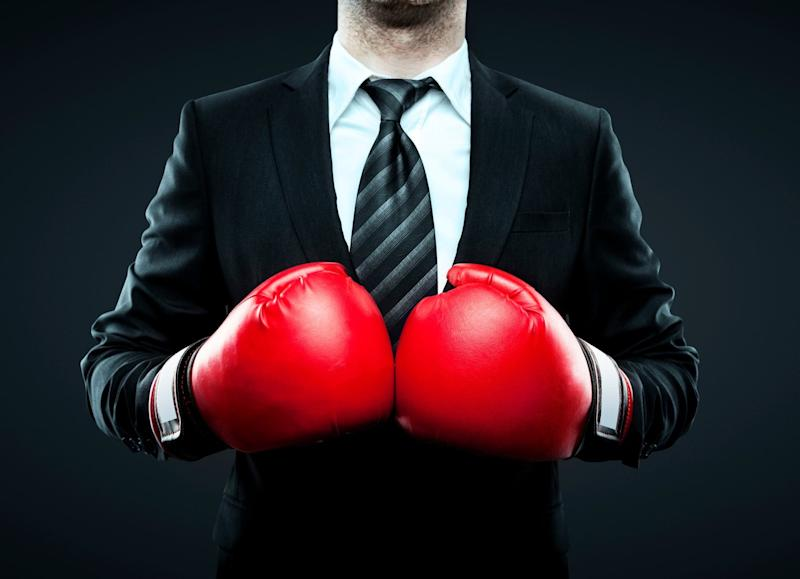 A man is a business suit is wearing boxing gloves.