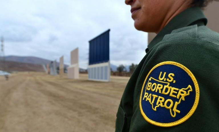 A US Border Patrol officer stands near prototypes of President Donald Trump's proposed wall, in San Diego, California in November 2017 (AFP Photo/FREDERIC J. BROWN)