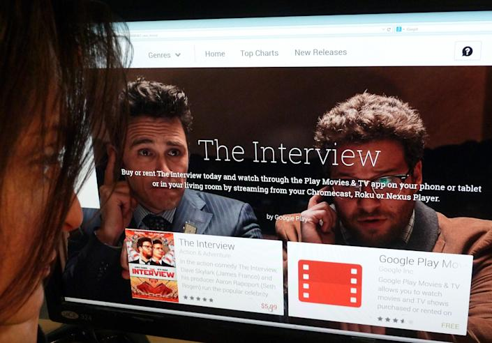 """A woman looks at the Google Play purchase page for the Sony film """"The Interview"""" in Washington, DC., on December 24, 2014 (AFP Photo/)"""