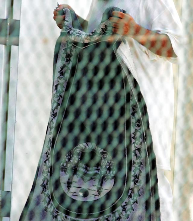 GUANTANAMO BAY, CUBA - AUGUST 26: A detainee walks with a prayer rug at Camp 4 of the maximum security prison Camp Delta at Guantanamo Naval Base August 26, 2004 in Guantanamo Bay, Cuba. This week the U.S. Military held preliminary hearings for four detainee's charged with conspiricy to commit war crimes. (Photo by Mark Wilson/Getty Images)
