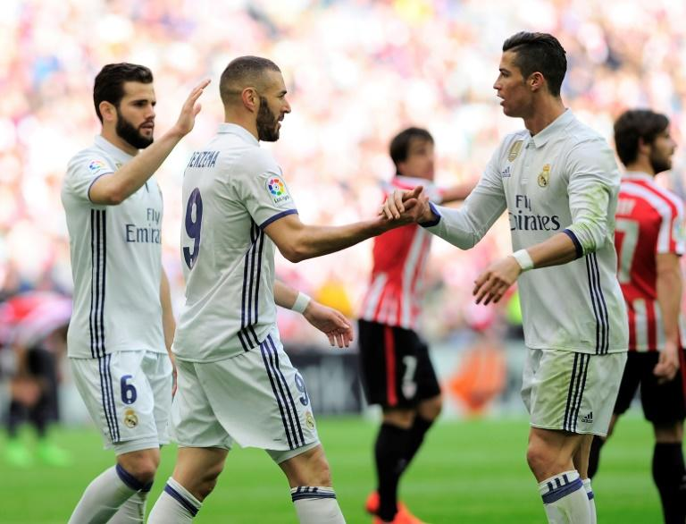 Real Madrid's forward Karim Benzema (C) is congratulated by teammates Cristiano Ronaldo (R) and defender Nacho Fernandez after scoring on March 18, 2017