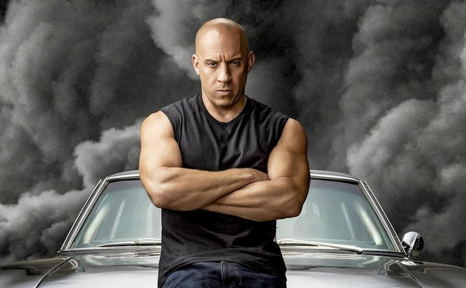 Vin Diesel in a black sleeveless t-shirt standing against a black car with black smoke behind it