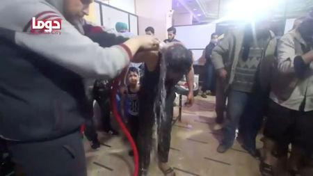 A man is washed following alleged chemical weapons attack, in what is said to be Douma
