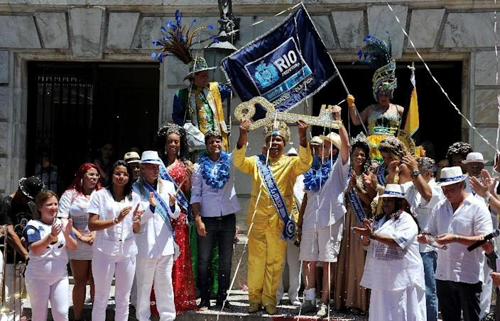 Carnival King Momo receives the keys to the city from from Rio's mayor Eduardo Paes (C-R) during the official launching of the 2016 Carnival in Rio de Janeiro on February 5, 2016 (AFP Photo/Tasso Marcelo)