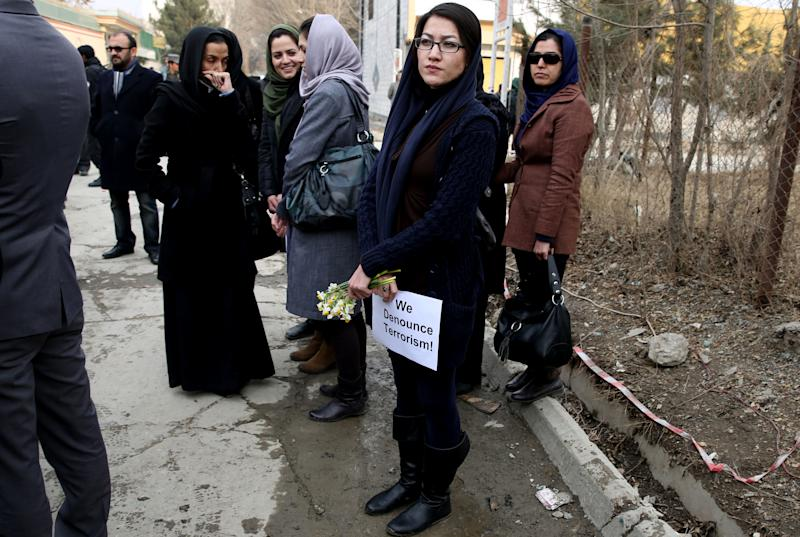 An Afghan member of a civil society organization, center, holds flowers outside of the La Taverna du Liban restaurant, during an anti terrorism demonstration in Kabul, Afghanistan, Sunday, Jan. 19, 2014. Hundreds of Afghans gathered outside a Lebanese restaurant in Kabul on Sunday to protest against Taliban attack that killed 21 people. The assault Friday by a Taliban bomber and two gunmen against the La Taverna du Liban restaurant was deadliest single attack against foreign civilians in the course of a nearly 13-year U.S.-led war there now approaching its end. They chanted slogans against terrorism as they laid flowers at the site of the attack. The dead included 13 foreigners and eight Afghans, all civilians. The attack came as security has been deteriorating and apprehension has been growing among Afghans over their country's future as U.S.-led foreign forces prepare for a final withdrawal at the end of the year. (AP Photo/Massoud Hossaini)