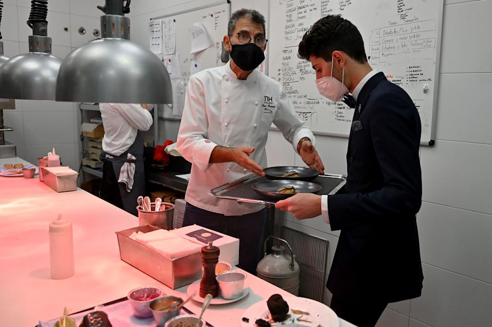 Spanish chef Paco Roncero puts dishes on a tray in his restaurant at the Casino of Madrid in the Spanish capital on November 13, 2020. - Spain has been one of the countries worst affected by the coronavirus pandemic and while its tourism-dependent economy generally did better in the third quarter, a resurgence in cases has led to new restrictions which many fear will once again hit business hard. (Photo by Gabriel BOUYS / AFP) (Photo by GABRIEL BOUYS/AFP via Getty Images)