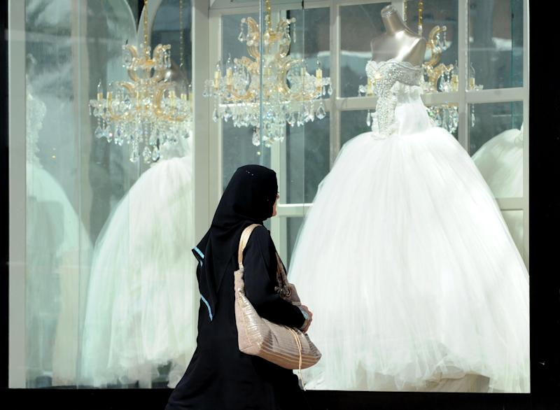 A Saudi woman walks past wedding dresses displayed in a shop window at a mall in Riyadh on February 4, 2013