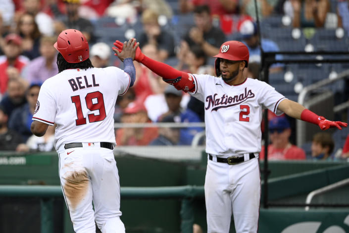 Washington Nationals' Josh Bell (19) is greeted by Luis Garcia (2) as he scores on a single by Yadiel Hernandez during the third inning of a baseball game against the Chicago Cubs, Sunday, Aug. 1, 2021, in Washington. (AP Photo/Nick Wass)