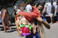 A devotee carries an idol of elephant-headed Hindu god Ganesha to take home for worship during reimposed weekend lockdown to prevent the spread of coronavirus in Jammu, India Saturday, Aug. 22, 2020. (AP Photo/Channi Anand)