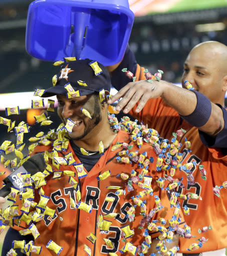 Houston Astros' Carlos Corporan, right, pours bubble gun over the head of Gregorio Petit, left, after a baseball game against the Toronto Blue Jays Friday, Aug. 1, 2014, in Houston. Petit hit a home run in the eighth inning to break a tie. The Astros won 3-1. (AP Photo/David J. Phillip)