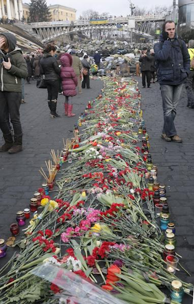 People lay down flowers on one of the streets leading to Independence Square, Kiev, the epicenter of the country's recent unrest, on a mourning day, Monday, Feb. 24, 2014. Ukraine's acting government issued a warrant Monday for the arrest of President Viktor Yanukovych, last reportedly seen in the pro-Russian Black Sea peninsula of Crimea, accusing him of mass crimes against protesters who stood up for months against his rule. (AP Photo/Efrem Lukatsky)