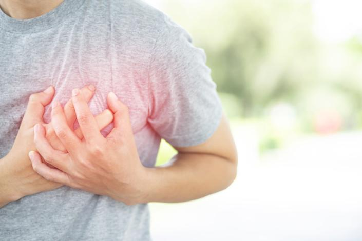Both hands grasp the left chest of a person with chest pain.