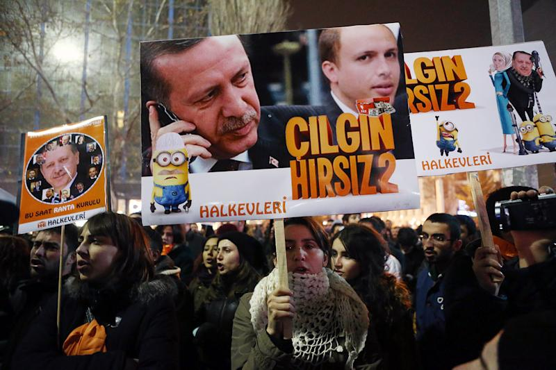 """People hold placards with images of Turkish President Recep Tayyip Erdogan and his son Bilal Erdogan that read """"Crazy thief"""" as they protest against corruption in Ankara, on December 17, 2014 (AFP Photo/Adem Altan)"""