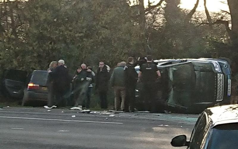 The scene of Prince Philip's car crash. He is in the centre, wearing a green jacket, and his Land Rover is seen on its side