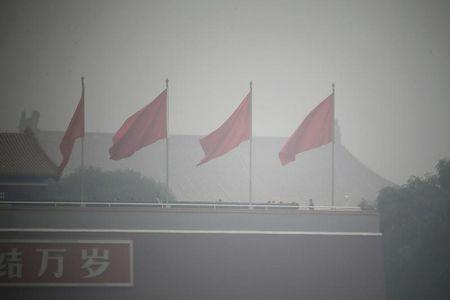 FILE PHOTO: Red flags flutter on Tiananmen Gate during a heavily hazy day in Beijing October 24, 2014. REUTERS/Jason Lee