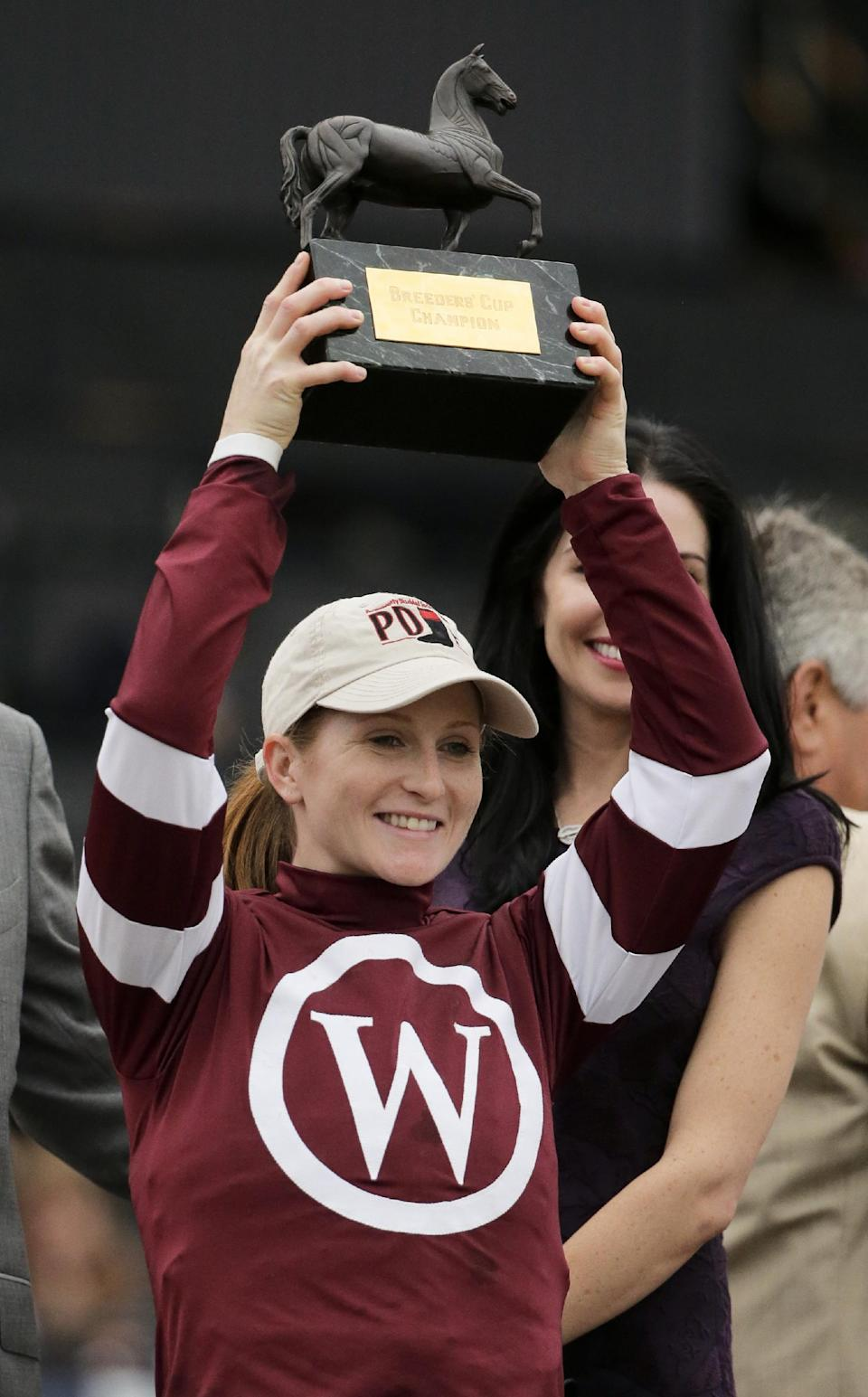 Rosie Napravnik celebrates with the trophy after riding Untapable to victory in the Breeders' Cup Distaff horse race at Santa Anita Park Friday, Oct. 31, 2014, in Arcadia, Calif. (AP Photo/Jae C. Hong)