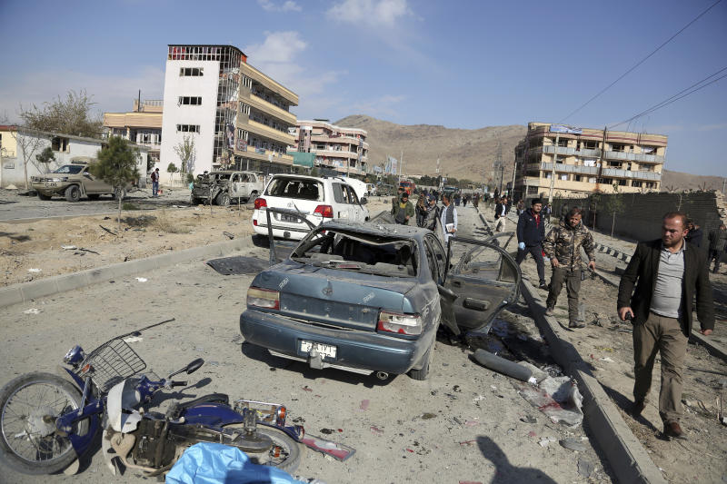 FILE- in this Wednesday, Nov. 13, 2019, file photo, Afghan security personnel gather at the site of a car bomb attack in Kabul, Afghanistan. Afghanistan will need vast amounts of foreign funding to keep its government afloat through 2024, a U.S. agency said Thursday, even as foreign donors are increasingly angry over the cost of debilitating corruption and the U.S. seeks a peace deal with Taliban to withdraw its troops. (AP Photo/Rahmat Gul, File)