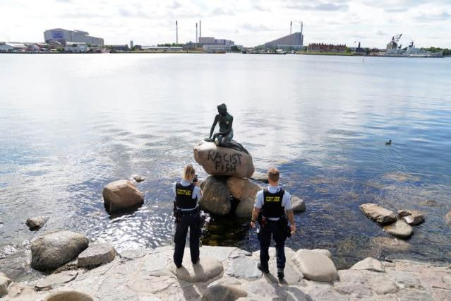 """Police officers stand in front of a graffiti reading """"Racist Fish"""" written on a statue of """"The Little Mermaid"""" in Copenhagen"""