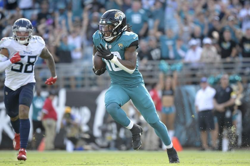 Jacksonville Jaguars wide receiver Laviska Shenault Jr. (10) runs in front of Tennessee Titans outside linebacker Harold Landry (58) after catching a pass during the second half of an NFL football game, Sunday, Oct. 10, 2021, in Jacksonville, Fla. (AP Photo/Phelan M. Ebenhack)