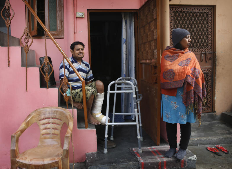 In this Feb. 20, 2014 photo, Indian man Ashok Yadav sits on a staircase outside his house, with his wife Laxmi Yadav beside him at a leper colony in New Delhi, India. The stigma of leprosy endures in India, even though the country has made great strides against the disease, which is neither highly contagious nor fatal. Now the number of new annual cases has risen slightly after years of steady decline, and medical experts say the enormous fear surrounding leprosy is hindering efforts to finally eliminate it.(AP Photo/Manish Swarup)