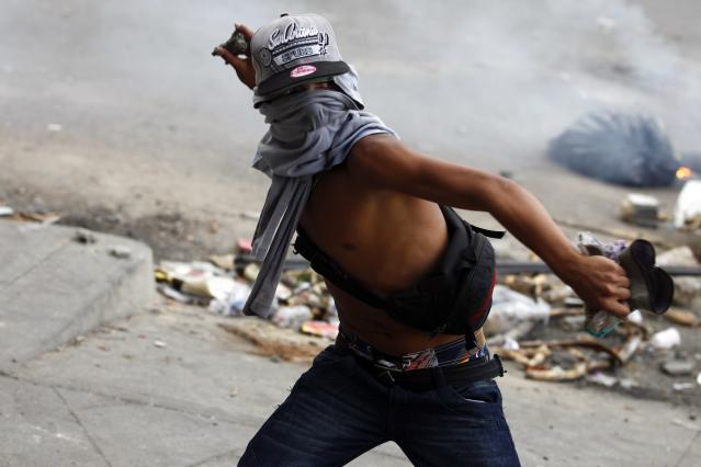 An anti-government protester throws stones at police during riots at Altamira square in Caracas March 6, 2014. A Venezuelan soldier and a motorcyclist died in a confused melee sparked by the opposition's barricading of a Caracas street, officials said on Thursday, boosting the death toll from nearly a month of violence to 20. Demonstrators have for weeks staged rallies and set up barricades to demand the resignation of President Nicolas Maduro, leading to clashes with security forces and government supporters. REUTERS/Carlos Garcia Rawlins (VENEZUELA - Tags: POLITICS CIVIL UNREST)