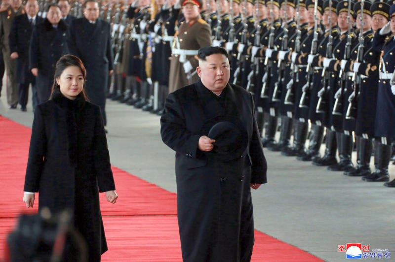 """In this Monday, Jan. 7, 2019, photo provided on Tuesday, Jan. 8, 2019, by the North Korean government, North Korean leader Kim Jong Un walks with his wife Ri Sol Ju at Pyongyang Station in Pyongyang, North Korea, before leaving for China. While President Donald Trump waits in the wings, Kim arrived in Beijing on Tuesday for his fourth summit with China's Xi Jinping, yet another nod to the leader Kim most needs to court as he tries to undermine support for international sanctions while giving up little, if any, ground on denuclearization. Independent journalists were not given access to cover the event depicted in this image distributed by the North Korean government. The content of this image is as provided and cannot be independently verified. Korean language watermark on image as provided by source reads: """"KCNA"""" which is the abbreviation for Korean Central News Agency. (Korean Central News Agency/Korea News Service via AP)"""