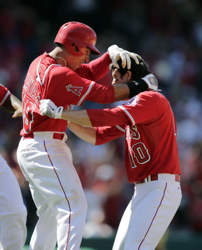 Los Angeles Angels' Grant Green, right, celebrates his ninth-inning walk-off single with Efren Navarro in a baseball game against the Seattle Mariners on Sunday, July 20, 2014, in Anaheim, Calif. The Angles won 6-5. (AP Photo/Jae C. Hong)
