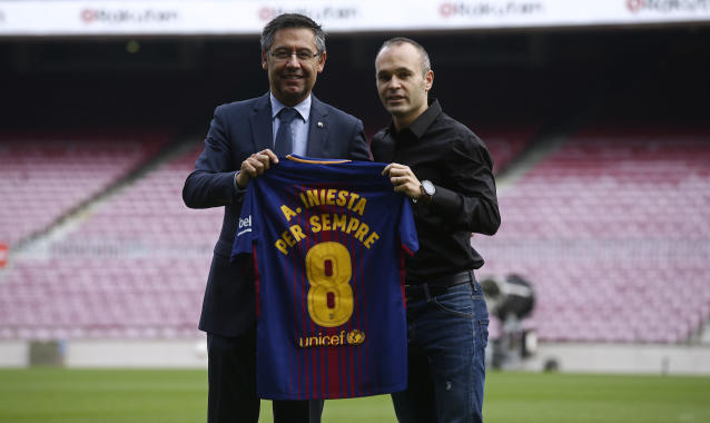 """FC Barcelona's Andres Iniesta, right, and FC Barcelona's president Josep Maria Bartomeu pose with a shirt reading in Catalan: """"Andres Iniesta forvever"""" at the Camp Nou stadium in Barcelona, Spain, Friday, Oct. 6, 2017. Barcelona has extended Andres Iniesta's contract """"for life"""". (AP Photo/Manu Fernandez)"""