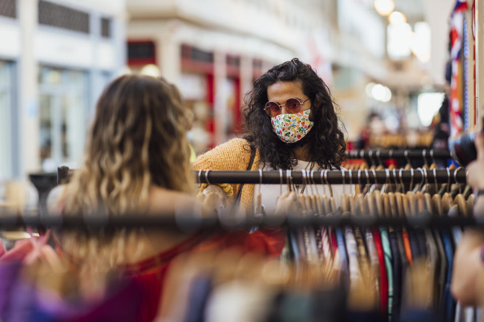 A shot of a young caucasian hipster woman and her mid adult Pakistani boyfriend looking at second hand, recycled clothing at a small local business in a market. They are wearing casual bohemian clothing, accessories, eyewear and reusable protective face masks.
