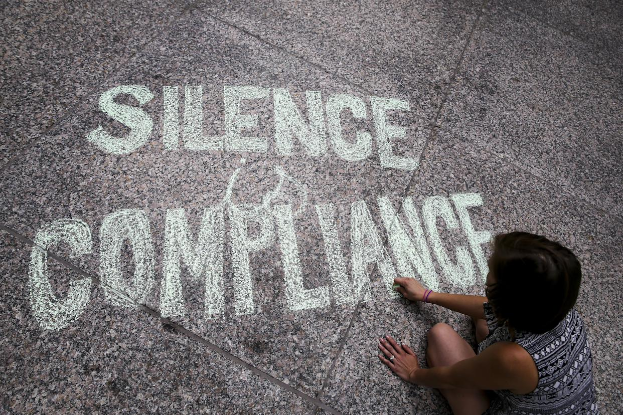 """A woman writes """"Silence is Compliance"""" with a chalk on the ground at Federal Plaza Square in Chicago during anAug. 13 protest in response to the violence that erupted in Charlottesville."""