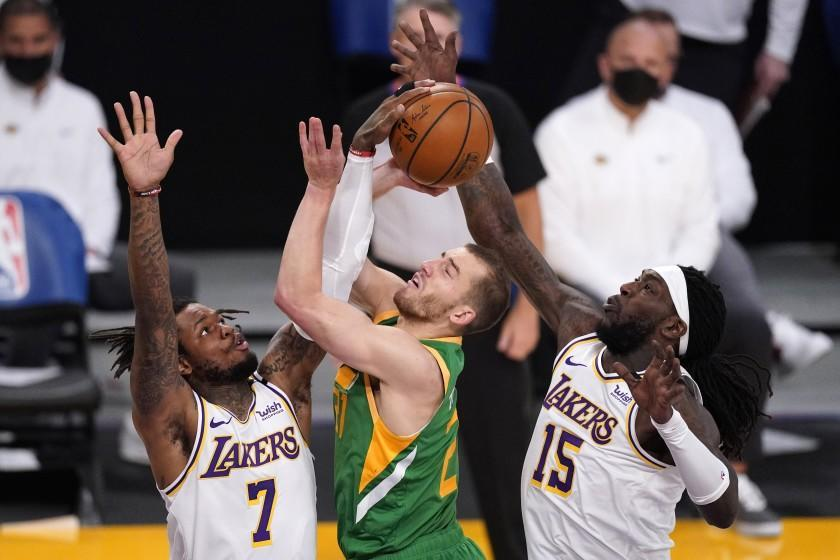 Utah Jazz guard Matt Thomas, center, has his shot blocked by Los Angeles Lakers guard Ben McLemore, left, as center Montrezl Harrell helps defend during the first half of an NBA basketball game Saturday, April 17, 2021, in Los Angeles. (AP Photo/Mark J. Terrill)