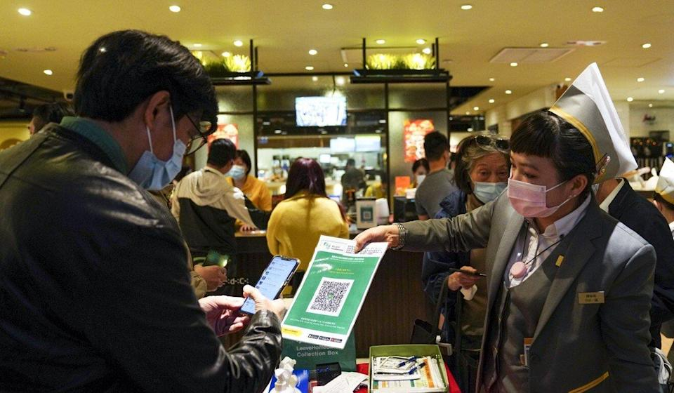 An employee presents a customer with the QR code for the government's Leave Home Safe app at a restaurant at Admiralty on Thursday. Photo: Sam Tsang