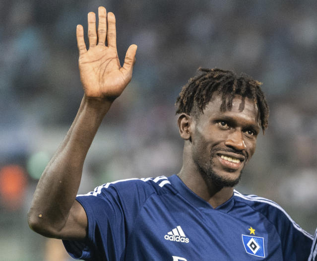 FILE - In this Aug. 11, 2019 file photo Hamurg's Bakery Jatta waves to fans after a match of Chemnitz against Hamburg in Chemnitz, Germany. Hamburger SV has reinforced its support for midfielder Bakry Jatta as the dispute over his identity continues to inflame tempers in Germanys second division. The affair began with a report by Sport Bild magazine suggesting that Jatta who became the first refugee to play in the Bundesliga when he made his debut for Hamburg in April 2017 has been playing under a false name and is in fact two years older than he claims to be. (Robert Michael/dpa via AP)