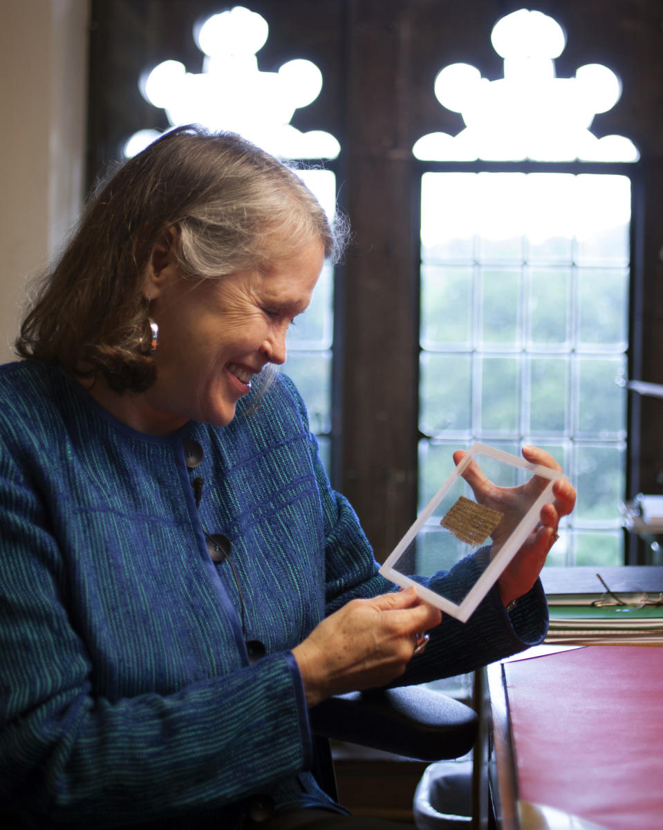 """In this Sept. 5, 2012 photo released by Harvard University, divinity professor Karen L. King holds a fourth century fragment of papyrus that she says is the only existing ancient text that quotes Jesus explicitly referring to having a wife. King, an expert in the history of Christianity, says the text contains a dialogue in which Jesus refers to """"my wife,"""" whom he identified as Mary. King says the fragment of Coptic script is a copy of a gospel, probably written in Greek in the second century. (AP Photo/Harvard University, Rose Lincoln)"""