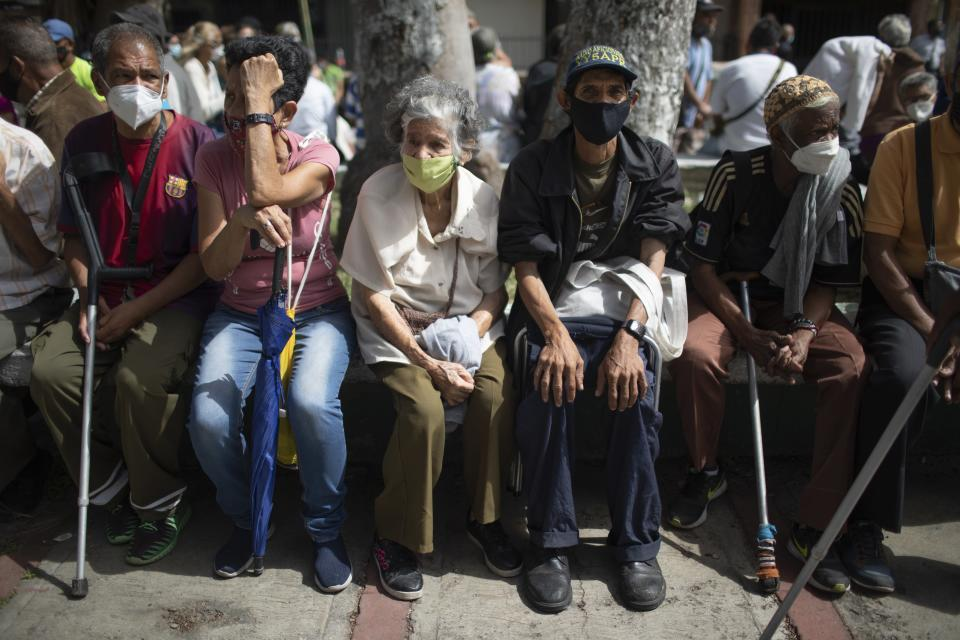 Seniors sit next to a basketball court in the 23 de Enero neighborhood to be vaccinated during a COVID-19 vaccination drive for seniors and those considered high risk for contagion in Caracas, Venezuela, Wednesday, June 9, 2021. ( AP Photo/Ariana Cubillos)